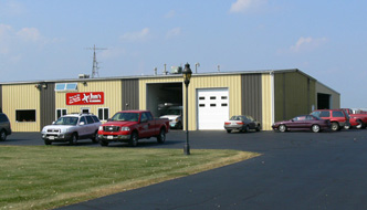 Metal building with garage doors and cars parked out front with the Jim's Plumbing sign on the side of the building